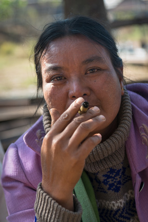cheroot: INLE LAKE, MYANMAR (BURMA) - 07 JAN 2014: Local Burmese Intha market woman smoke cheroot cigar with scale details on front. Selective focus on the eyes.