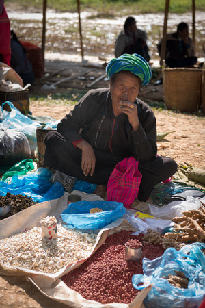 inle: INLE LAKE, MYANMAR (BURMA) - 07 JAN 2014: Local Burmese Intha woman smoke cheroot cigar and sell  on a traditional open market. Local markets serves most common shopping needs Inle Lake people.