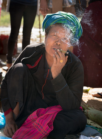 cheroot: INLE LAKE, MYANMAR (BURMA) - 07 JAN 2014: Local Burmese Intha woman smoke cheroot cigar. Cheroots are Burmese facial feature.
