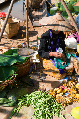 inle: Asian woman in a hat sell fresh vegetable and fruit on a traditional open market.