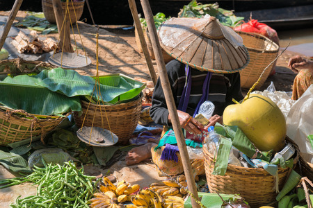 Local Burmese Intha woman sell vegetable on a traditional open market in dollars. Local markets serves most common shopping needs Inle Lake people.