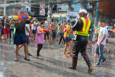 Phuket, Thailand - April 13, 2014: Tourist and police officer celebrate Songkran Festival, the Thai New Year by splashing water to each others on Patong streets.