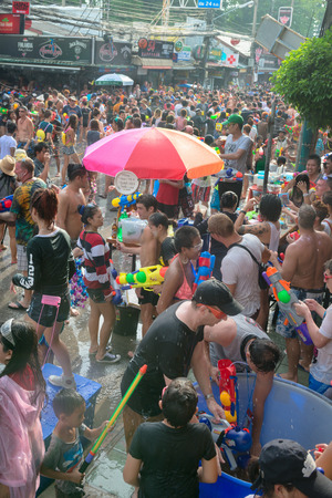 Phuket, Thailand - April 13, 2014: Tourists and residents celebrate Songkran Festival, the Thai New Year by splashing water to each others on Patong streets.