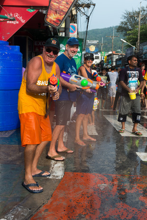 Phuket, Thailand - April 13, 2014: Tourists celebrate Songkran Festival, the Thai New Year by splashing water to each others on Patong streets.