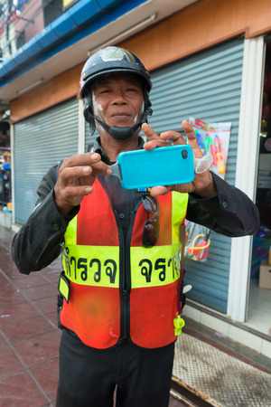 Phuket, Thailand - April 13, 2014: Police officer shows how to protect phone during celebration Songkran Festival, the Thai New Year from splashing water.