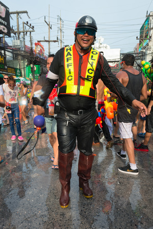 Phuket, Thailand - April 13, 2014: Police officercelebrate Songkran Festival, the Thai New Year by splashing water to each others on Patong streets.