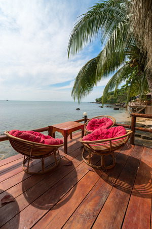 Relaxing lounge chair relax area in beach cafe by the blue sea photo