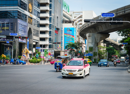 BANGKOK, THAILAND - 21 NOV 2013  Taxi and traditional tuk-tuk pass on crossroads street with skytrain track on background