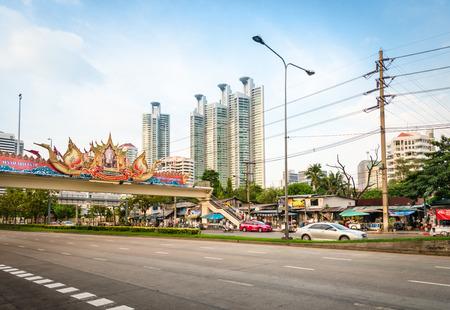 BANGKOK, THAILAND - 21 NOV 2013  Wide street under bridge with portrait of the King of Thailand Bhumibol Adulyadej  Rama IX  and modernt buildings skyscrapers on background