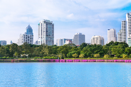 Modern city skyline of living district with park and lake in front  in day under blue sky photo