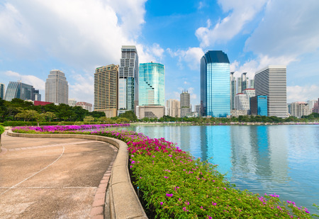 Modern city skyline of business district downtown with park running and walking track near lake in day under blue sky photo