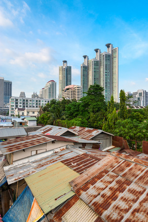 dissension: Modern asian city discord with run-down shacks and high-tech skyscrapers on background Stock Photo