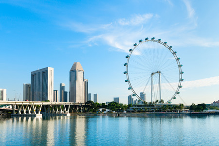 Big ferris wheel in the modern city skyline and bay water on front, Singapore.