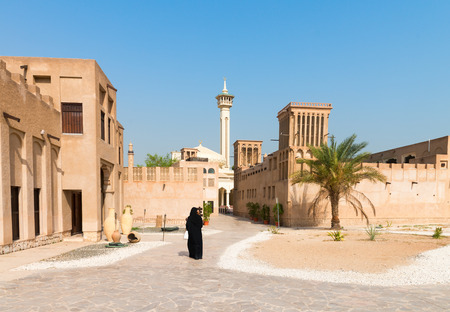 windtower: Woman in traditional muslim black dress in old arabic city district with mosque minaret on background