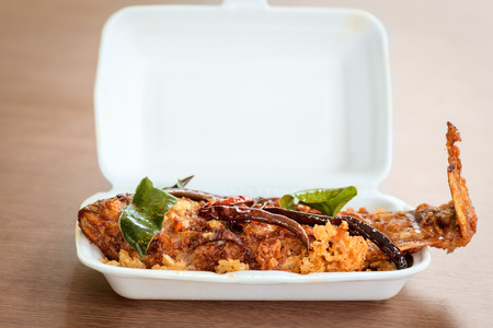 Sour fried full cooked fish with spicy hot red chili pepper in white take away bowl on wooden table photo