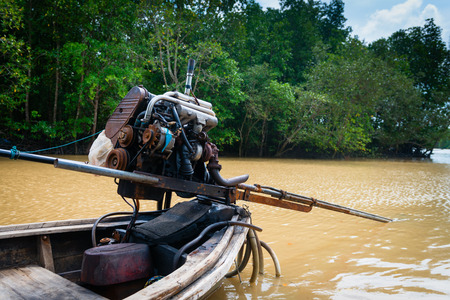 boat motor: Traditional long tail wooden boat motor against tropical river and mangrove on background, Thailand Stock Photo
