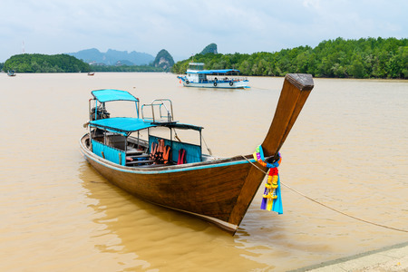 nam: Traditional wooden decorated boat on tropical river with Krabi landmark (Khao Kanab Nam cliff) on background, Krabi Town, Thailand Stock Photo