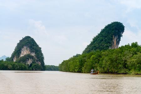 nam: Two limestone cliffs above tropical river with mangrove and small wooden boat. Krabi landmark Khao Kanab Nam cliff, Krabi Town, Thailand.