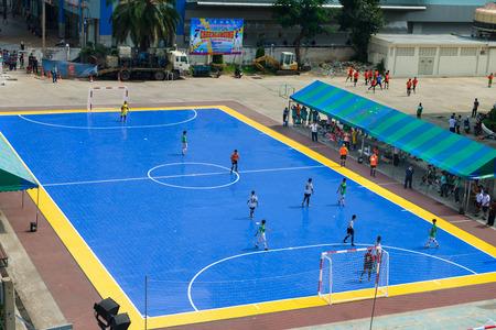 sportsmen: BANGKOK, THAILAND - 21 NOV 2013: Sportsmen train on blue outdoor stadium in front of sport science bureau of Sports Authority of Thailand (SAT) near National stadium