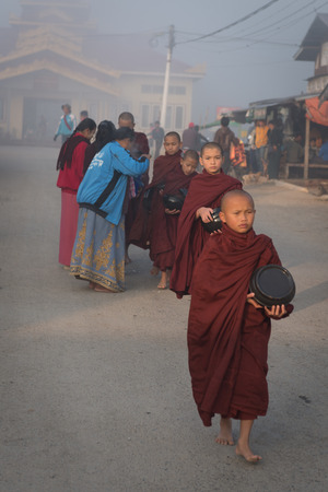 recolectar: LAGO INLE, MYANMAR - 08 JAN 2014: los monjes j�venes se re�nen comida en pedir limosna madrugada. Ofrecer comida es uno de los rituales m�s antiguos y comunes en el budismo. Editorial
