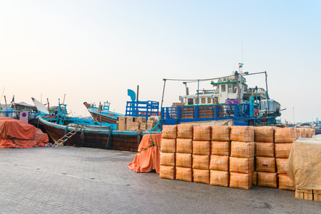 traditional goods: DUBAI, UAE - 16 JULY 2014: Dubai Creek port with moored up traditional dhows wooden boats and different goods on the pier, United Arab Emirates Editorial