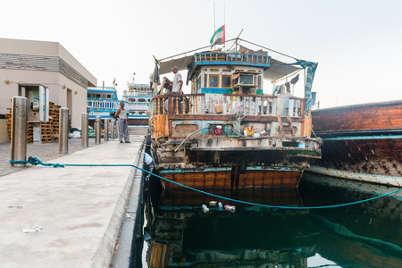 decrepit: DUBAI, UAE - 16 JULY 2014: Very old and decrepit traditional dhows wooden boat stands moored up at Dubai Creek wharfage, United Arab Emirates