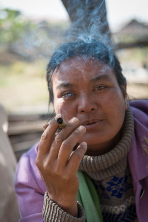 cheroot: INLE LAKE, MYANMAR (BURMA) - 07 JAN 2014: Local Burmese Intha market woman smoke cheroot cigar with scale details on front. Selective focus on the hand.