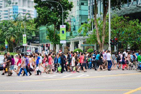 SINGAPORE - 01 JAN 2014: Crowd on pedestrians crossing on famous street Orchard Road in Singapore. Orchard Road is the most popular shopping enclave of Singapore and major tourist attraction.