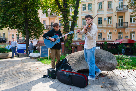 passerby: KIEV, UKRAINE - SEP 16, 2013: Street musicians play in front of passerby in the city central park Editorial