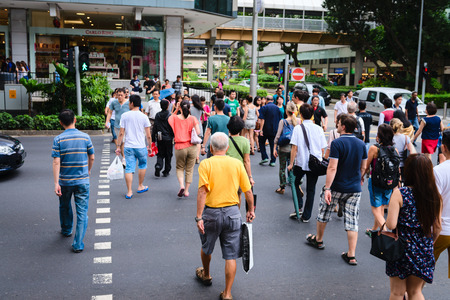 cross street: SINGAPORE - 01 JAN 2014: People on pedestrians crossing on famous street Orchard Road in Singapore. Orchard Road is the most popular shopping enclave of Singapore and major tourist attraction. Editorial