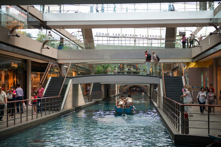 manmade: SINGAPORE - 01 JUN 2013: Interior of the Shoppes at Marina Bay Sands luxury shopping mall with man-made water canal and entertaining pleasure boat.