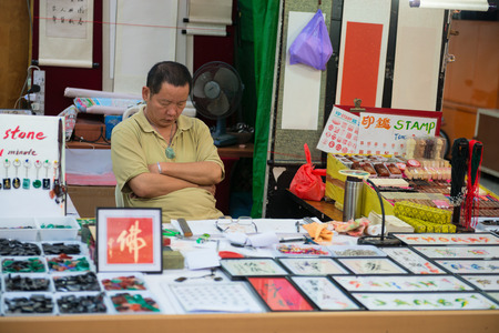 china stamps: SINGAPORE - 01 JUN 2013: Individual stamps resting seller on his store in China town tourist shopping area in Singapore