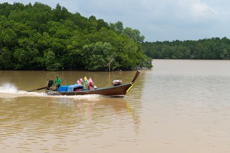 MOTORIZADO: Krabi Tailandia 14 OCT 2014: Los pescadores locales y su esposa crucero a lo largo del río de Krabi en Tailandia en su motor barco de madera hecho a mano con una carga de redes y boyas de señalización. Editorial