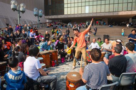 liu: HONG KONG CHINA  18 JAN 2015: Facilitator Channon Liu directs tourists and visitors as they participate in a drum circle at Kowloon Promenade in Hong Kong. Editorial