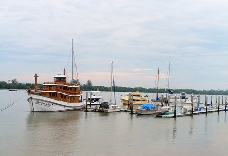 teakwood: KRABI THAILAND  15 OCT 2014: Beautiful teakwood luxury tour boat docked at a harbor with other boats on a cloudy day. Editorial