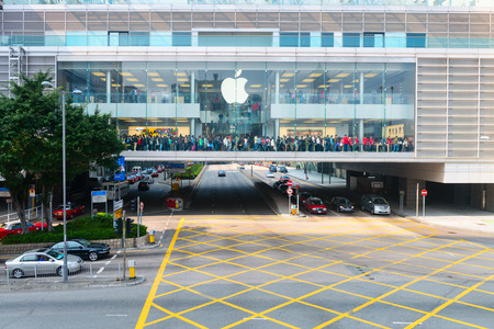 enormous: HONG KONG CHINA  18 JAN 2015: Enormous crowd of people crossing in front of an Apple store as they await entrance to a major downtown shopping center in Hong Kong China.