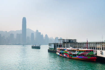 sha: HONG KONG CHINA  18 JAN 2015: A colorful ferry boat bound for Tsim Sha Tsui moored and waiting for passengers at the central ferry pier in Kowloon with the Hong Kong skyline in the background.