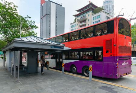 parada de autobus: SINGAPUR 02 JAN 2014: Un autob�s de dos pisos de color brillante deja a los pasajeros a lo largo de Hill Street en el centro de Singapur.