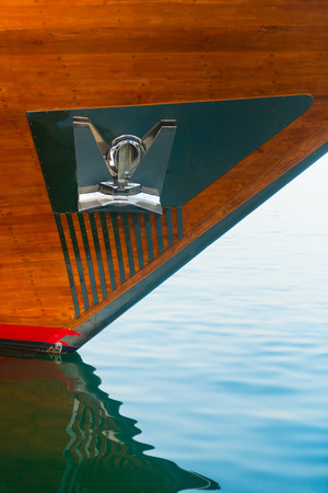 hull: Highly polished, stainless steel anchor and plate, mounted to the wooden hull of a luxury yacht at the bow. Stock Photo