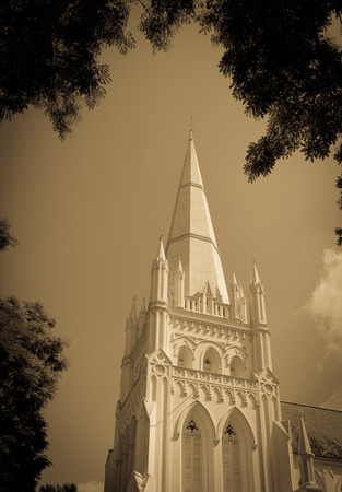 turret: High tower turret of the church under blue sky in green trees frame sepia toned