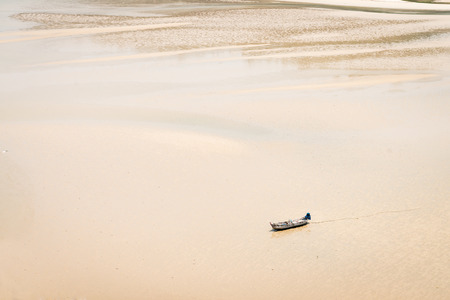 silty: Small, open motorboat, traveling alone over an open, shallow expanse of silty low water. Stock Photo