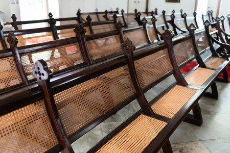 pews: Beautiful, antique, church pews, exquisitely handcrafted from stained hardwood and wicker, arranged in their traditional rows and still in use for religious services.