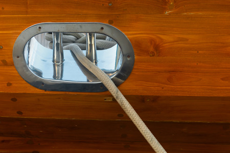 bulkhead: Mooring line, positioned through a stainless steel fairlead in the wooden bulkhead of a sailing yacht. Stock Photo