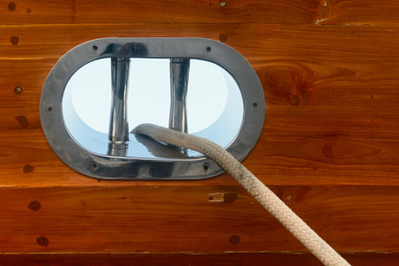 positioned: Mooring line, positioned through a stainless steel fairlead in the wooden bulkhead of a sailing yacht. Stock Photo
