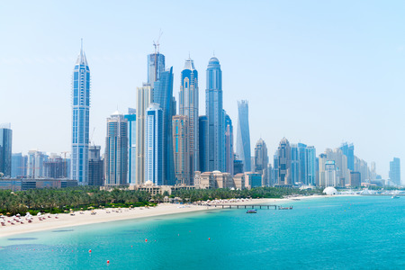 Tall skyscrapers of a modern metropolitan cityscape tower over a beautiful white sandy beach on a warm sunny day.