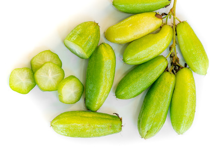 acidic: Highly sour and acidic fruit of tropical cucumber tree, native to Southeast Asia, displayed on a stem, harvested whole, and sliced in cross sections, displayed against a white background.