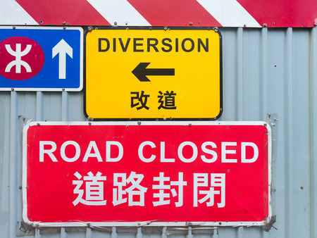 traffic signs: Brightly colored traffic signs announce a detour due to construction and development along a central street in downtown Hong Kong, China.