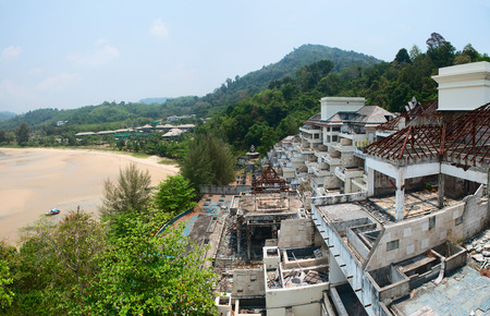 constructed: Partially constructed luxury beach resort development project, abandoned and overgrown by wild vegetation, on a hillside overlooking a wide, sandy beach.