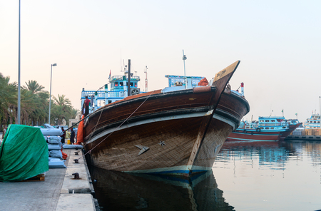 lading: DUBAI, UAE - 16 JULY 2014: Traditional dhows wooden boat lading at Dubai Creek port, United Arab Emirates Editorial