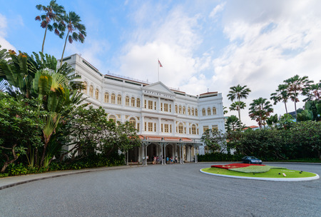 tree service pictures: SINGAPORE - 07 AUG 2015: Grand facade of the luxurious Raffles Hotel in downtown Singapore, with its beautiful gardens.